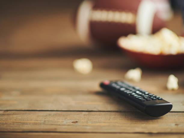 time to watch football on tv. remote control, popcorn and american football - telecomando background foto e immagini stock