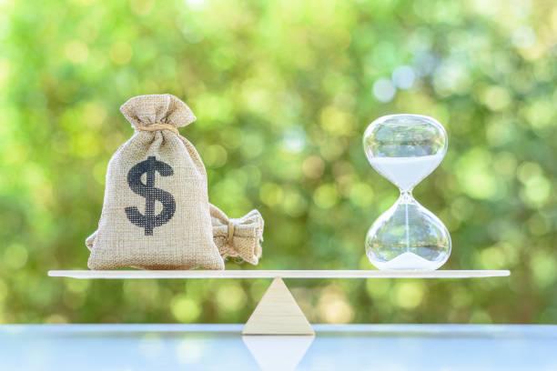 zeitwert des geldes, vermögenswachstum im zeitverlauf, finanzkonzept: dollarbeutel, sanduhr oder sanduhr auf einer waagenskala in gleicher position, zeigt investitionen in langfristiges eigenkapital für mehr geldwachstum - gleichgewicht stock-fotos und bilder