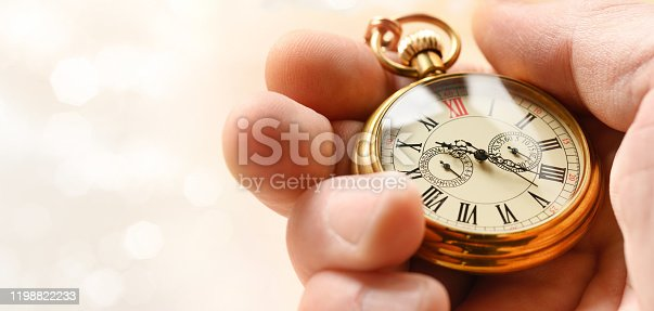 Time symbol concept. Retro gold pocket watch in hand.