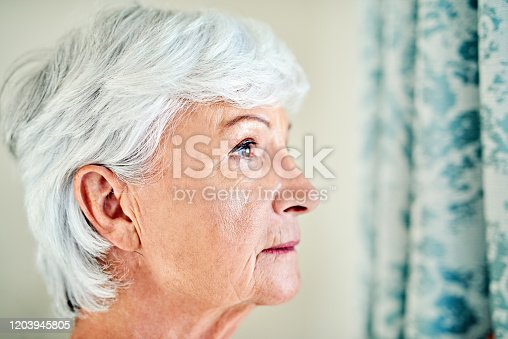 Shot of a senior woman looking thoughtfully out of a window at home