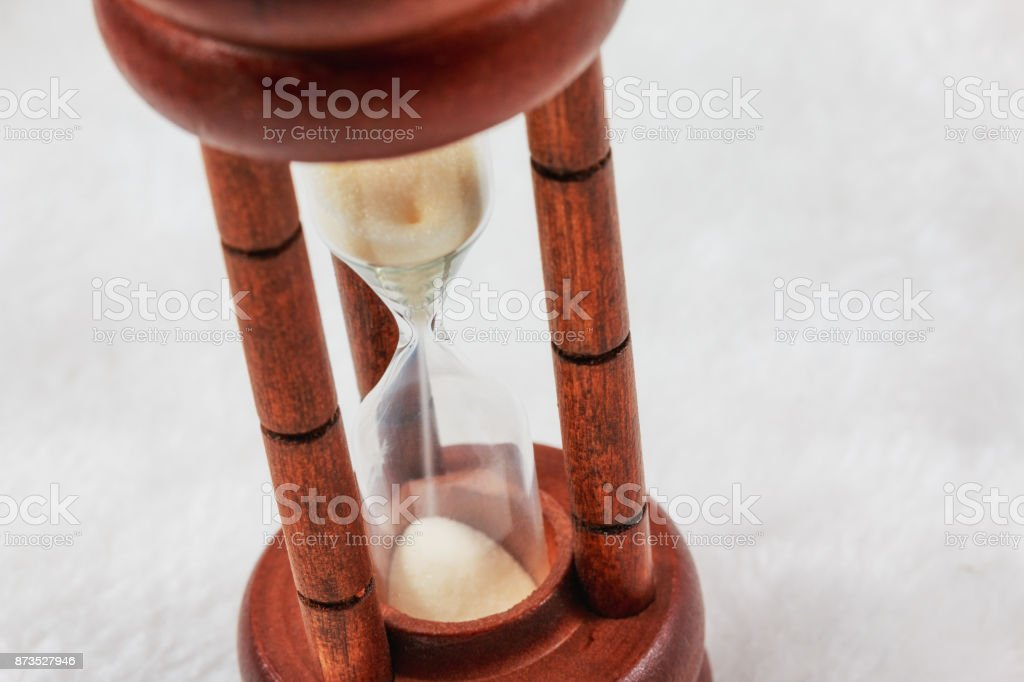 time with sandglass on the white wool fabric. Loss of opportunity with time is gone. stock photo