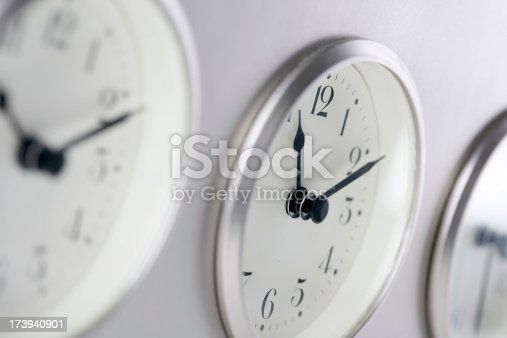 Three clock faces set to different time zones (very narrow field of focus).