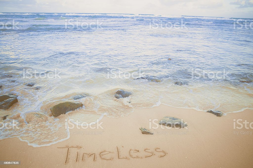 'Timeless' written in the sand royalty-free stock photo