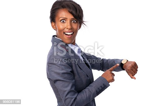 Studio shot portrait of a surprised businesswoman pointing her finger at the watch, looking at camera with a toothy smile and wide open eyes. Isolated on white background, with copy space for your message.