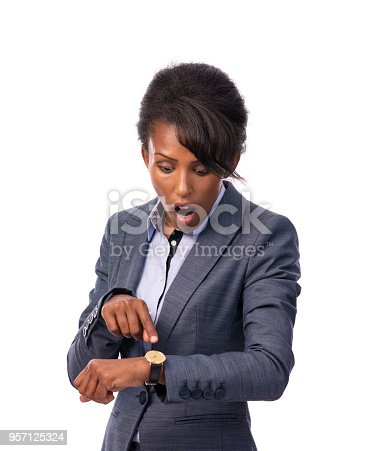 Surprised businesswoman with open mouth pointing over her clock, looking down at the watch. Cut out, isolated over white background, waist up portrait.