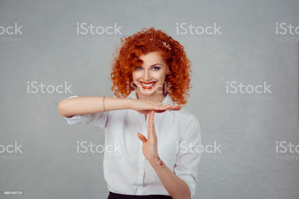 Timeout. Closeup portrait, young, happy, smiling woman showing time out gesture with hands isolated on gray wall background. Positive human emotion facial expressions, feeling body language reaction stock photo