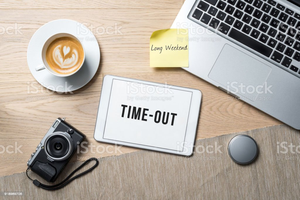 Time-out written on tablet in office as flatlay stock photo