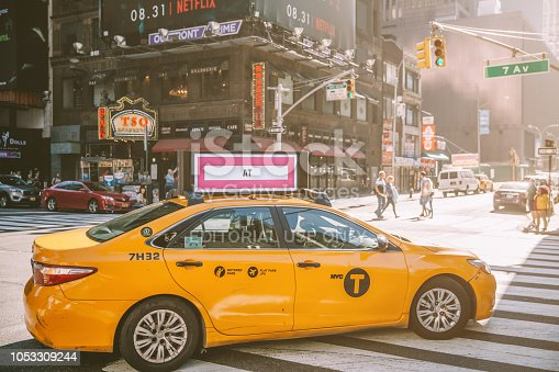 New York, United States - September 16, 2018: A yellow taxi at Times Square with tourists. Iconified as 'The Crossroads of the World' it's the brightly illuminated hub of the Broadway Theater District.