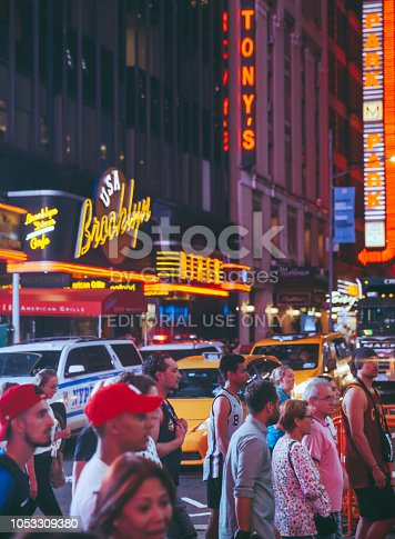 New York, United States - September 19, 2018: Times Square with tourists. Iconified as 'The Crossroads of the World' it's the brightly illuminated hub of the Broadway Theater District.