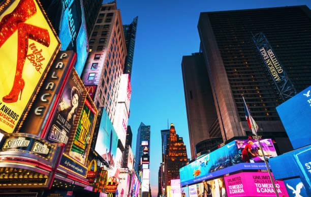 Times Square advertising illuminated at dusk - foto de acervo