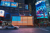 New York City, USA - May 31, 2013: People walking outside the Nasdaq stock exchange building at the Times Square in Manhattan New York City in the middle of the night, while a police car is passing by in front of a an american flag billboard.