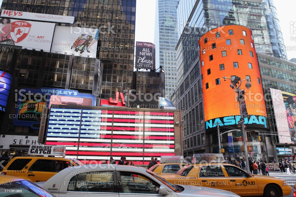 Times Square NYC taxi cabs and US flag NASDAQ stock photo