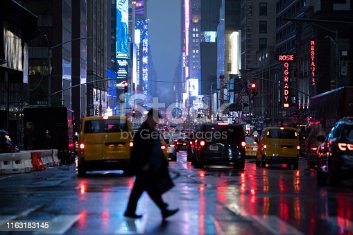 Person crossing the street in the rainy reflections of city lights from Times Square, New York City.