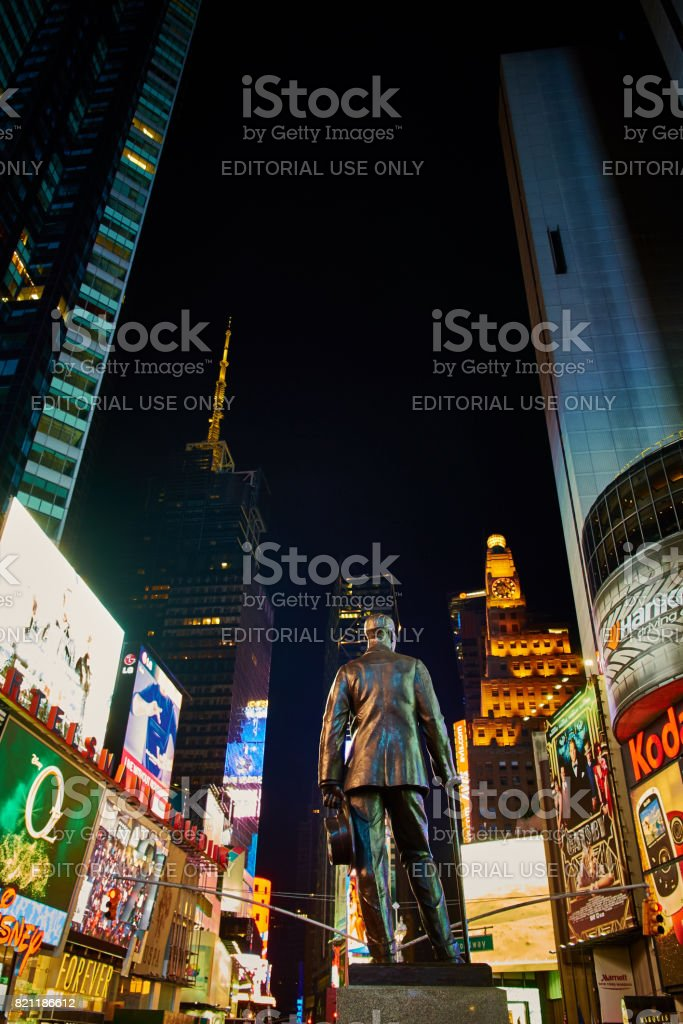 Times Square with Father Duffy sculpture on Manhattan surrounded by advertisings at night stock photo