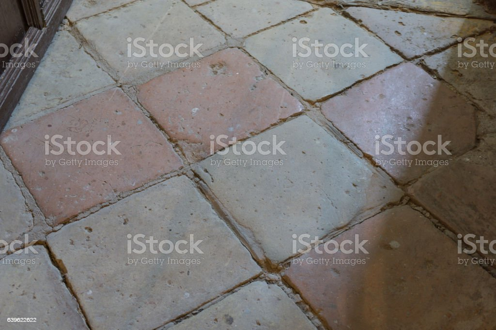 Timeworn Clay floor tiles, very old probably from the 18th stock photo