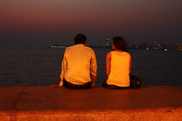Timid lovers by the sea Mumbai, India - March 7, 2013: A couple sitting along Marine drive in Mumbai India in the evening, watching the sunset.  romance stock pictures, royalty-free photos & images
