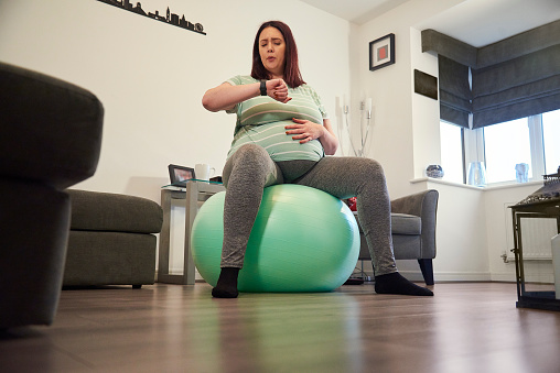 A pregnant lady sat on a gym ball in her living room timing contractions on her watch
