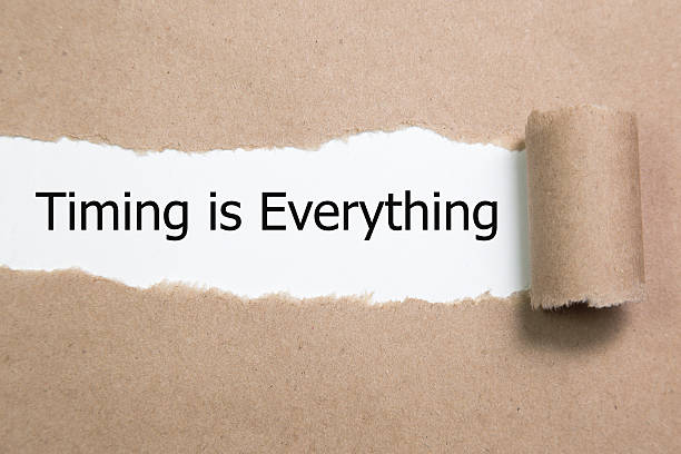 Timing is Everything, appearing behind torn paper. stock photo