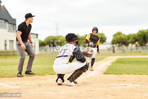 Full length shot of a young baseball player running on the pitch to reach base during a game outdoors