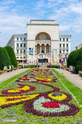 Timisoara, Romania - July 9, 2016: Timisoara  view showing Central Plaza with the view of Building of Romanian National Opera, Victory Square and garden, flowers, trees and people walking on the street can be seen on the background
