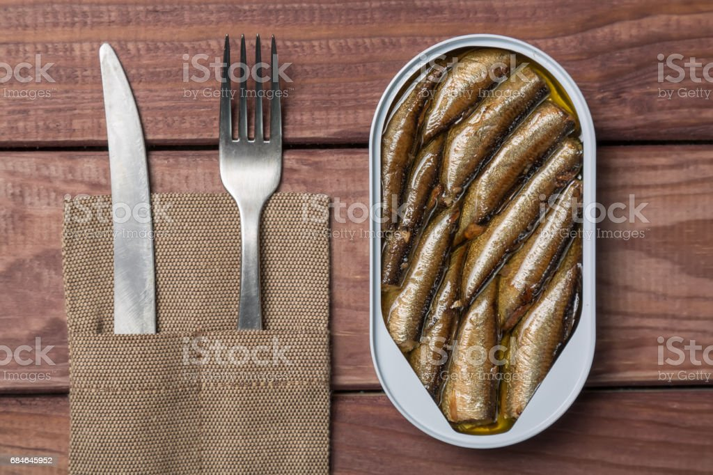 Tin can of sprats, sardines with knife and fork on wooden table. Top view stock photo