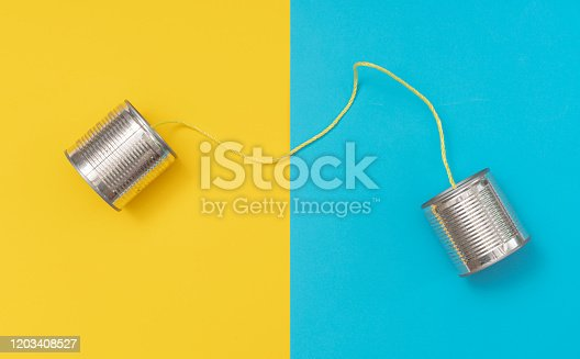 Tin can phone on yellow and blue paper backgrounds