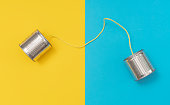 istock Tin can phone on yellow and blue paper backgrounds 1203408527