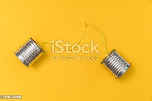 Tin can phone on yellow background