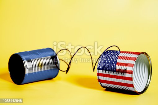 tin can phone with USA and Salvador Flags. communication concept on yellow