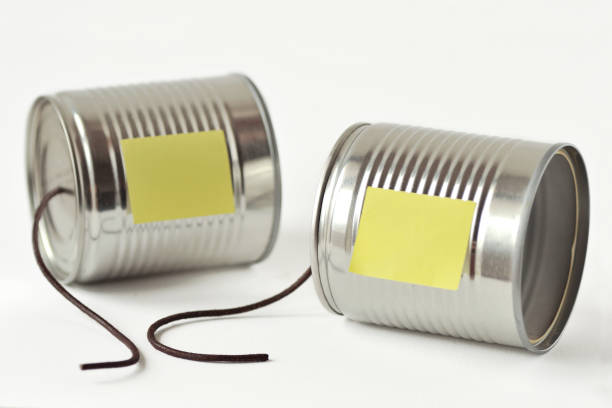 Tin cans phone with broken string and paper note - Communication concept stock photo