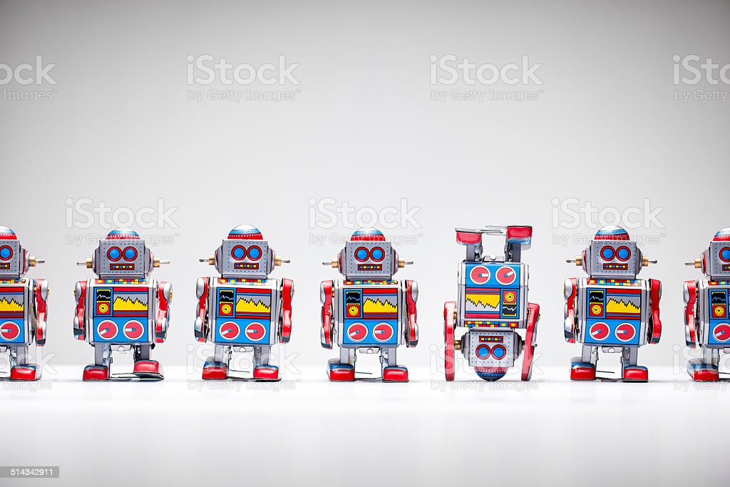 Tin toy robots - Upside down Concept photograph of retro tin robots standing in a row. One robot is standing upside down. 1950-1959 Stock Photo