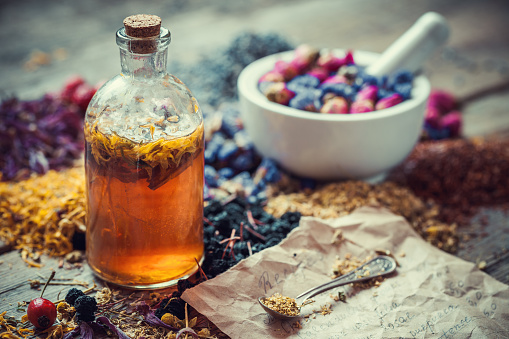 Tincture bottle, mortar of healing herbs and paper of recipes