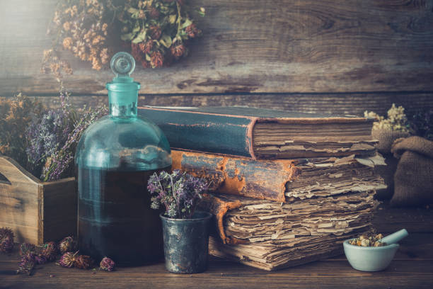 Tincture bottles, assortment of dry healthy herbs, old books, mortar, curative drugs. Herbal medicine. Retro styled. stock photo