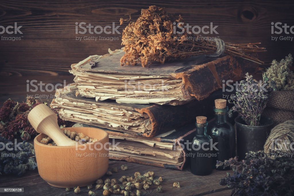 Tincture bottles, bunches of dry healthy herbs, stack of antique books, mortars, sack of medicinal herbs. Herbal medicine. stock photo