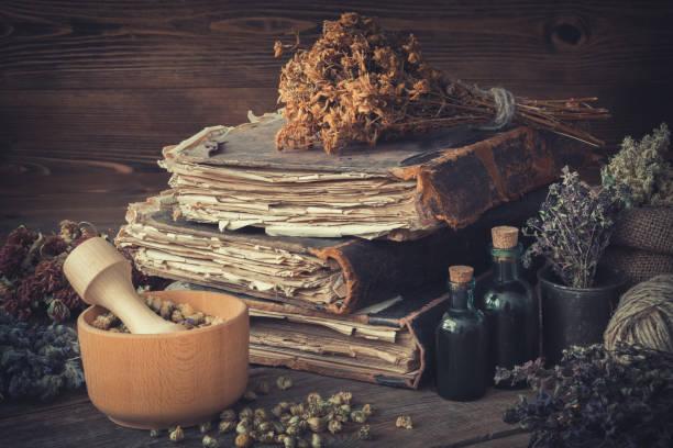 Tinktur Flaschen, bündeln von trockenen gesunden Kräutern, Stapel von antiken Büchern, Mörser, Plünderung Heilkräuter. Pflanzliche Arzneimittel. – Foto