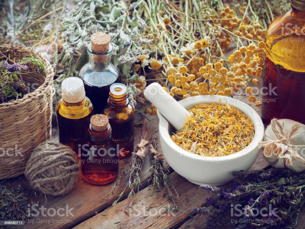 Tincture bottles, mortar of marigold flowers and healing herbs. stock photo