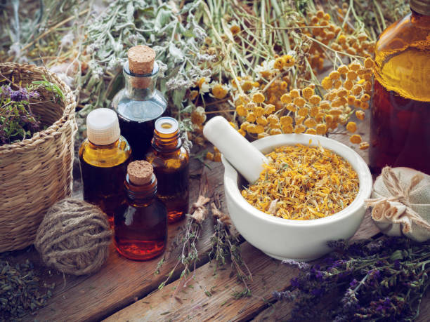 tincture bottles, mortar of marigold flowers and healing herbs. - holistic medicine stock photos and pictures