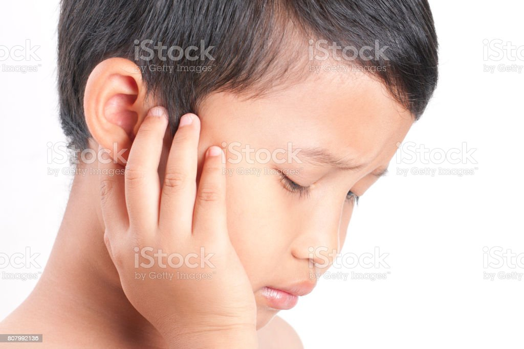 Tinnitus. Closeup up side profile sick boy having ear pain touching his painful head. stock photo