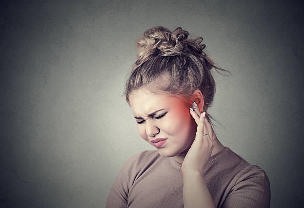 Tinnitus. Sick female having ear pain stock photo