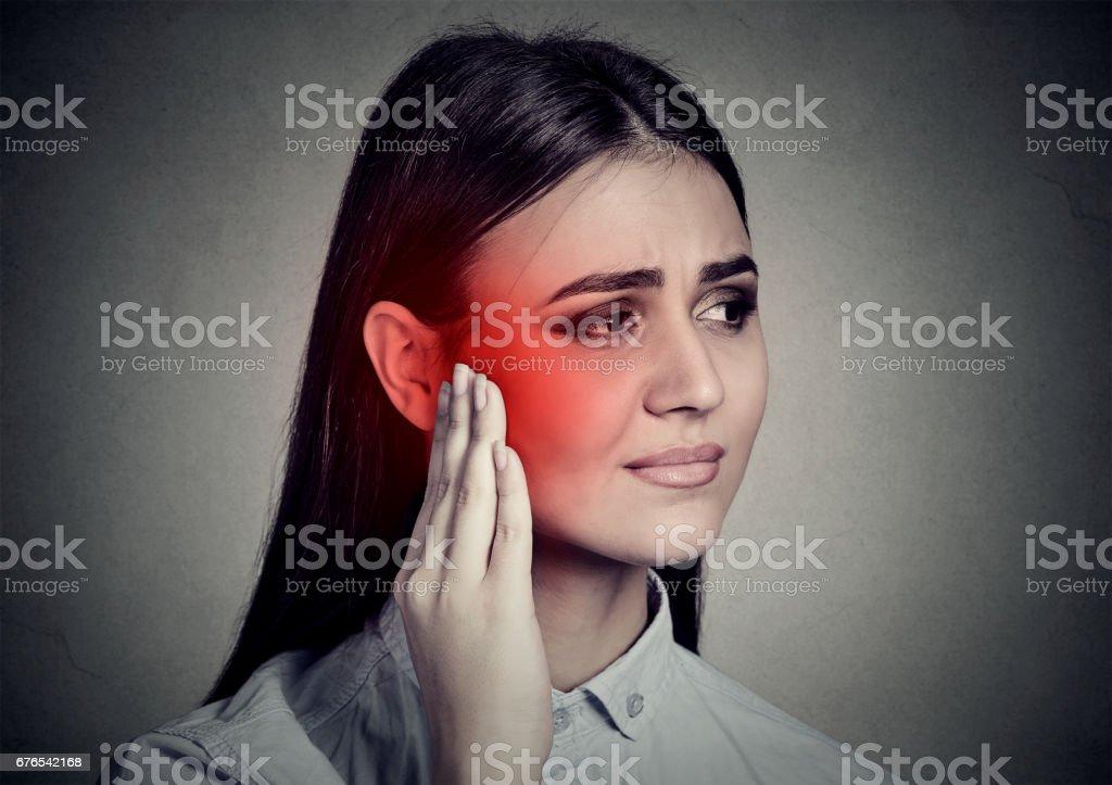Tinnitus. Sick woman having ear pain touching her temple stock photo