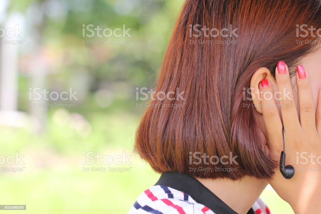 Tinnitus, young woman has pain in the ear stock photo