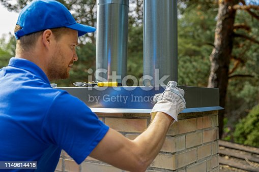 895571294 istock photo tinsmith on the roof installing tin cap on the brick chimney 1149614418