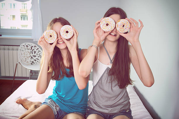 Tinted image two teen girls having fun with donuts Two teen girls having fun with donuts. tinted image. horizontal family having fun on the bed lifting legs stock pictures, royalty-free photos & images