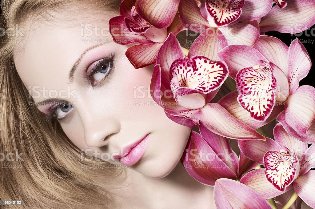 Tinted portrait of woman with pink orchids royalty-free stock photo