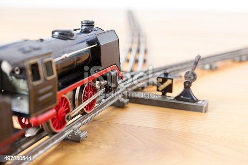 Little tin-toy locomotive on a railroad track close to a crossing. Close-up on a wooden floor.