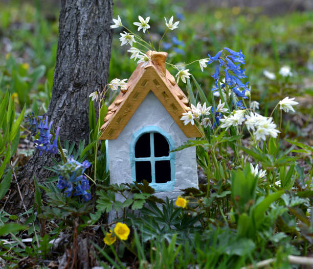 Tiny adorable fairy house under the tree in the garden. stock photo