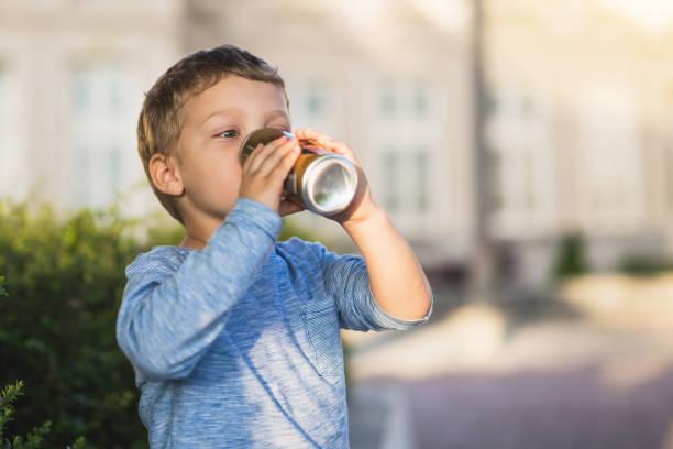 winziges baby jungen trinken säfte - innocent saft stock-fotos und bilder