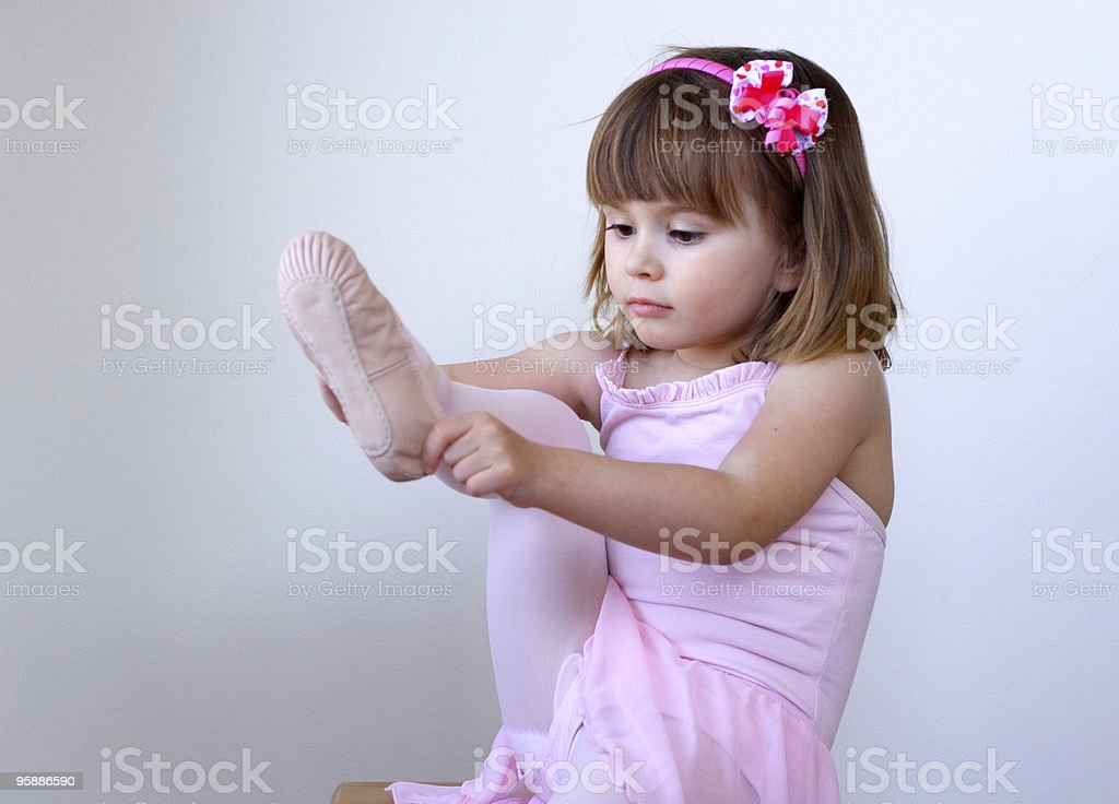 Tiny ballerina putting her slippers on stock photo