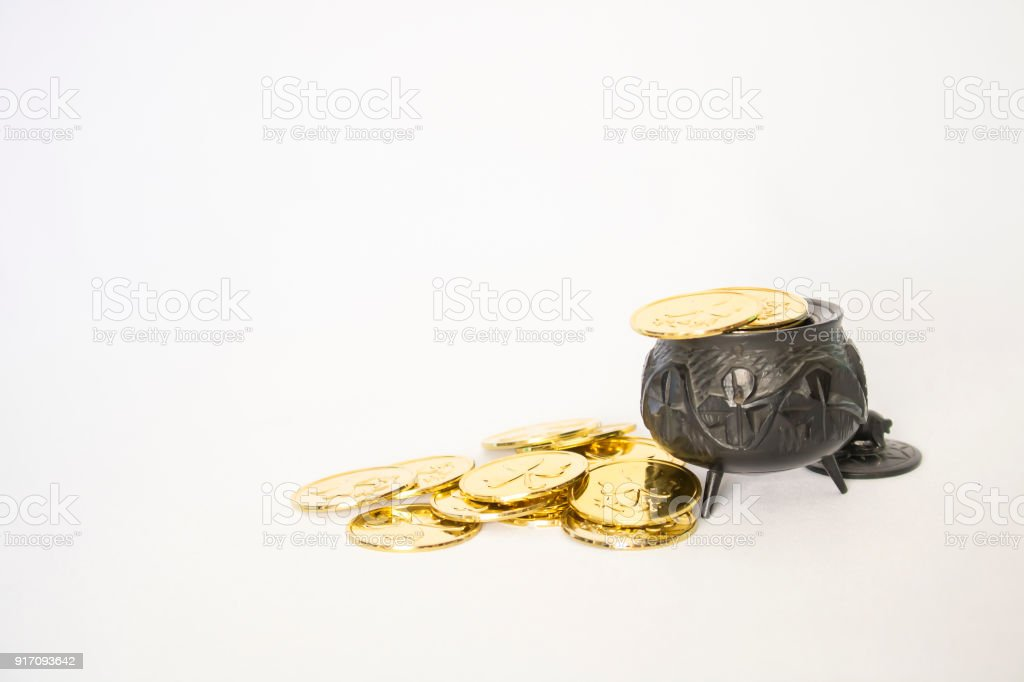 Tiny black Irish antique pot filled with gold coins on white background stock photo