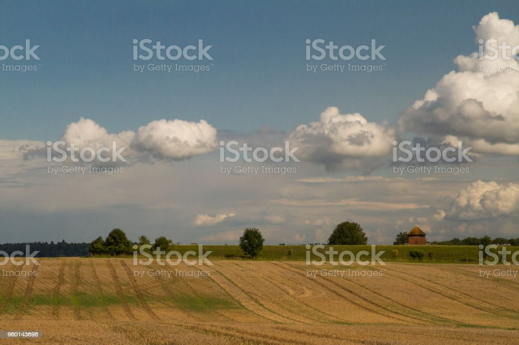 Tiny building on hillside under big sky by crop field stock photo